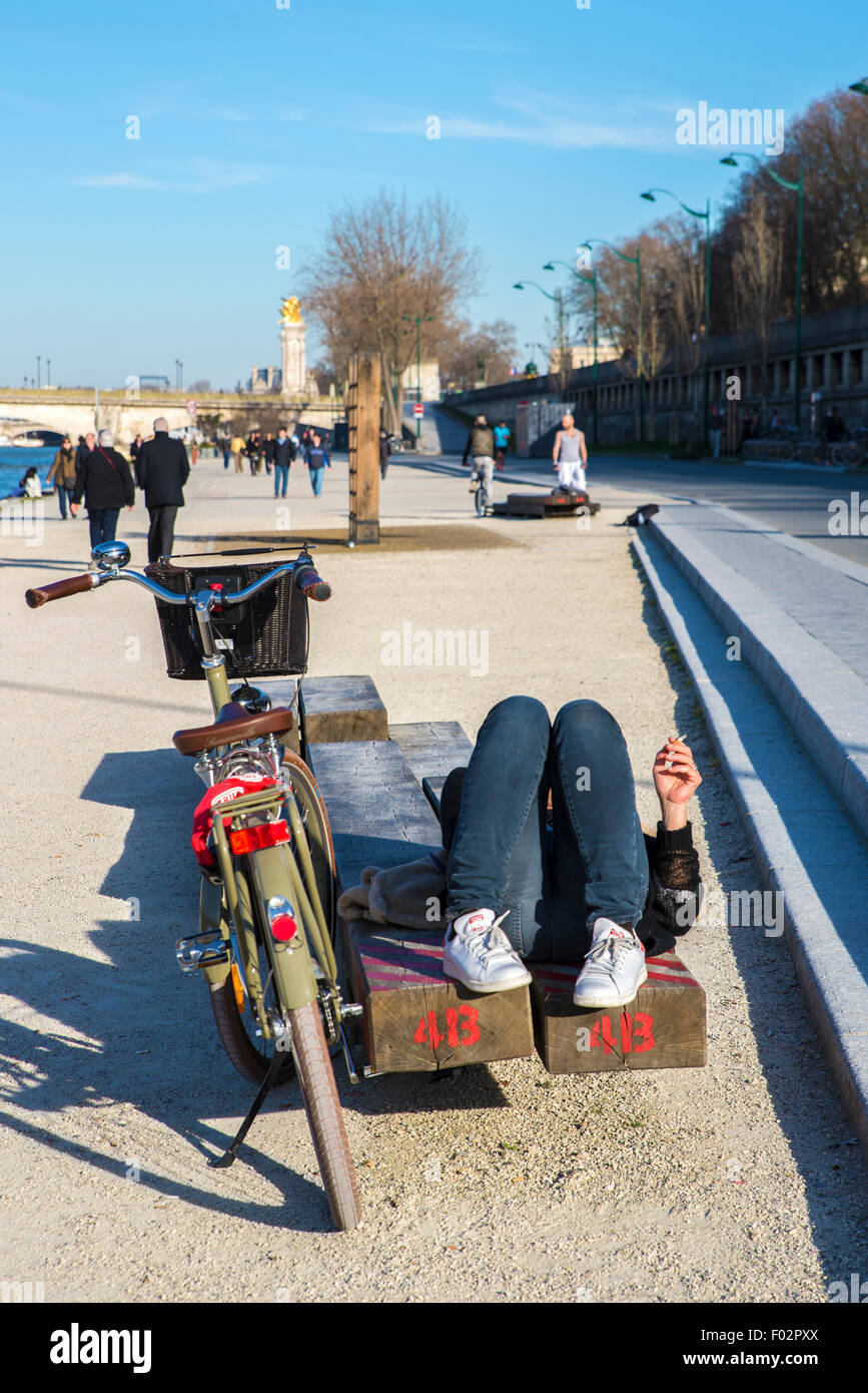 Woman lying on bench on the banks of the Seine, Pont des invalides bridge behind, Paris - Stock Image