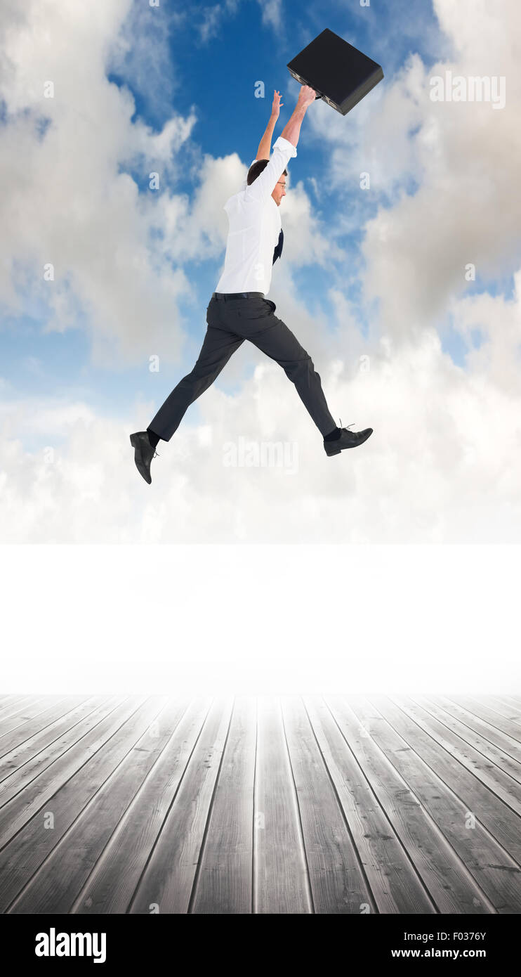 Composite image of businessman leaping with his briefcase - Stock Image