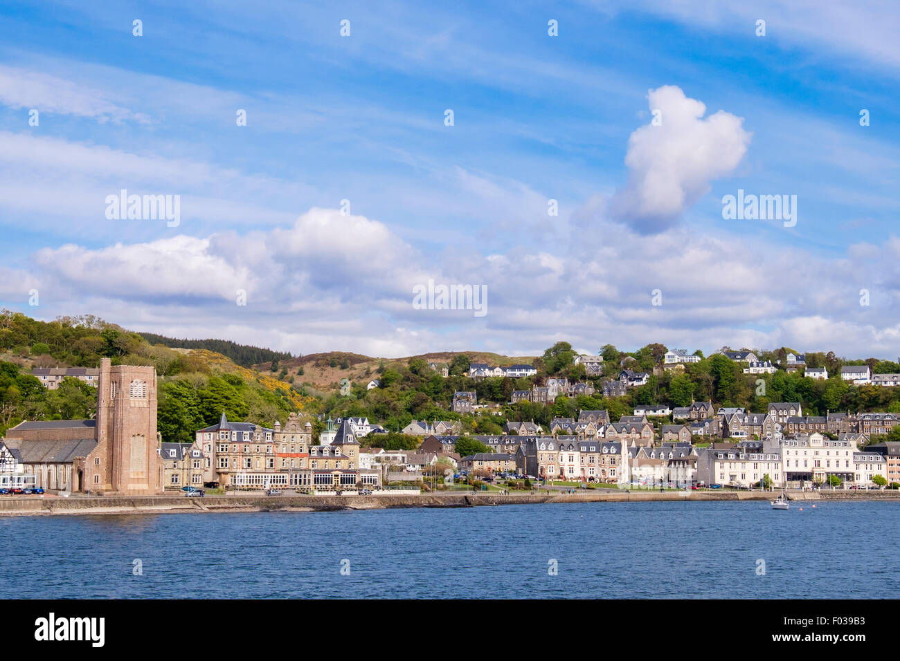Offshore view across sea to waterfront buildings and St Columba's Cathedral catholic church in Oban Argyll and - Stock Image