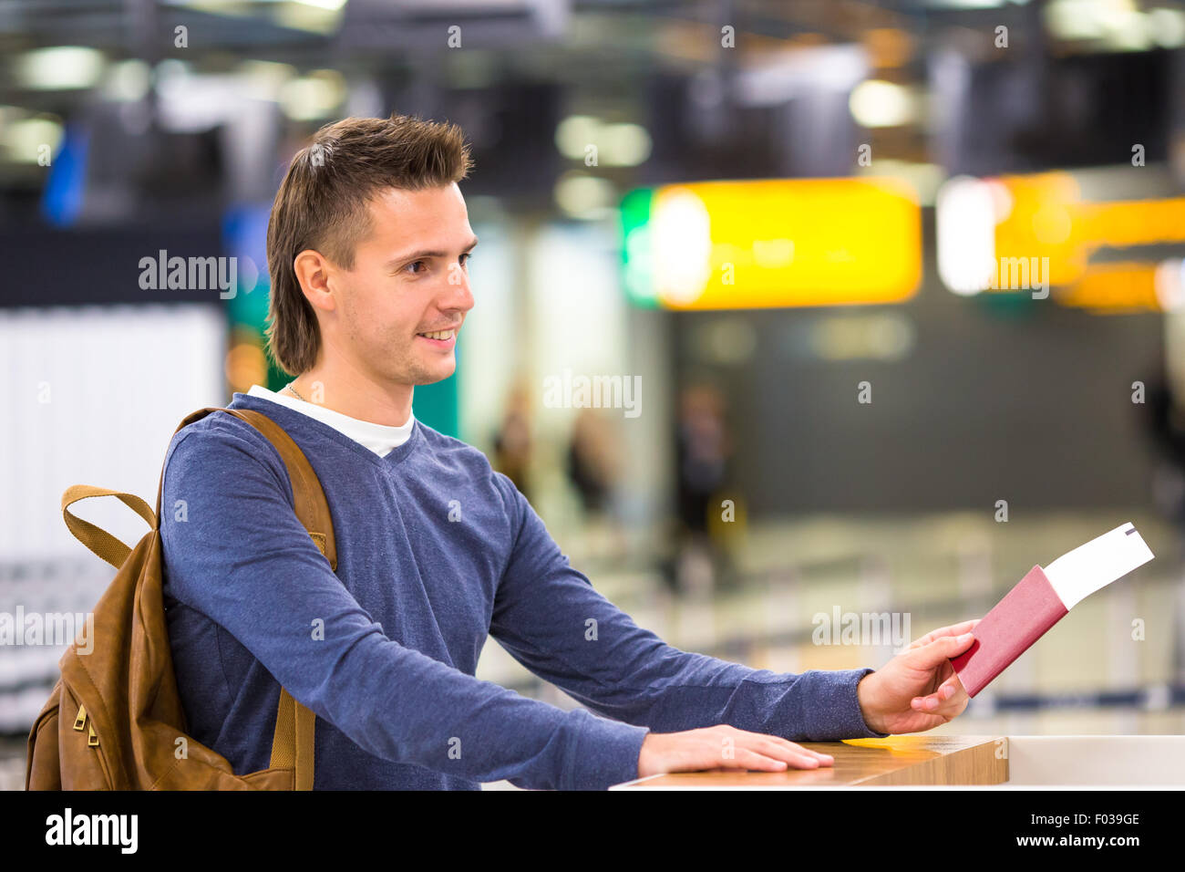 Beautiful man with passports and boarding passes at the front desk at airport - Stock Image
