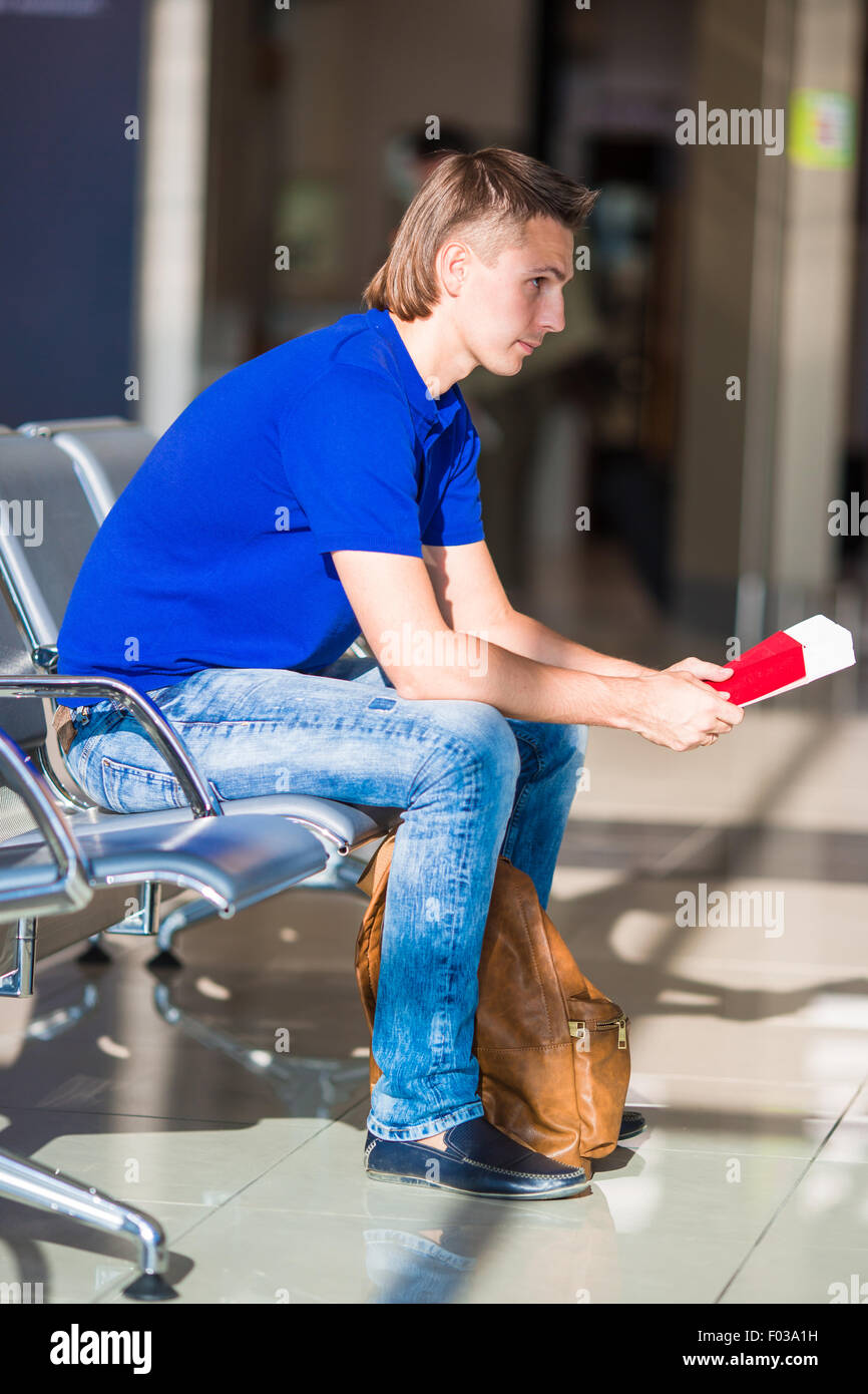 Young man holding passports and boarding pass at airport - Stock Image