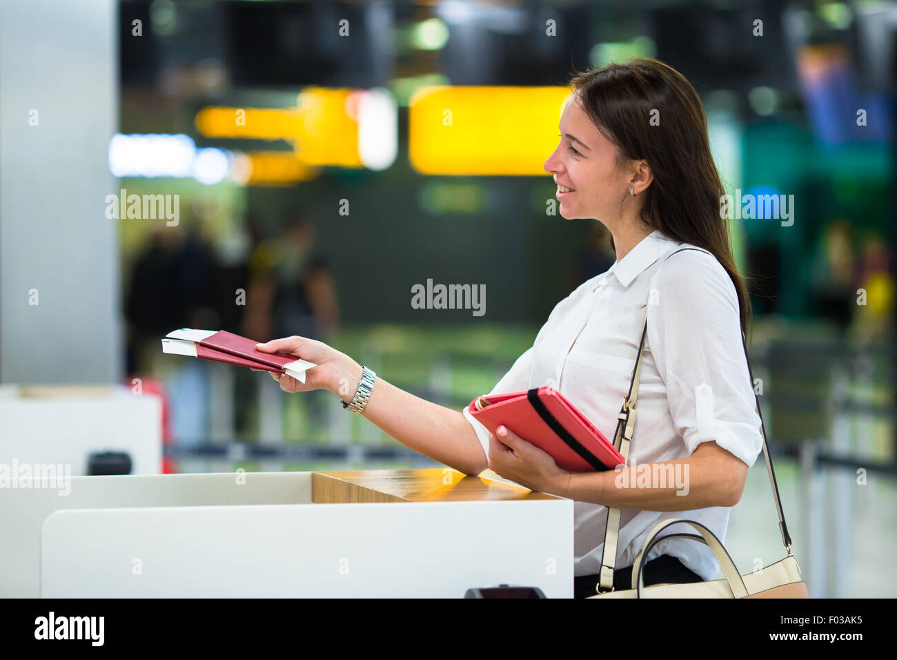 Young girl with passports and boarding passes at the front desk at international airport - Stock Image