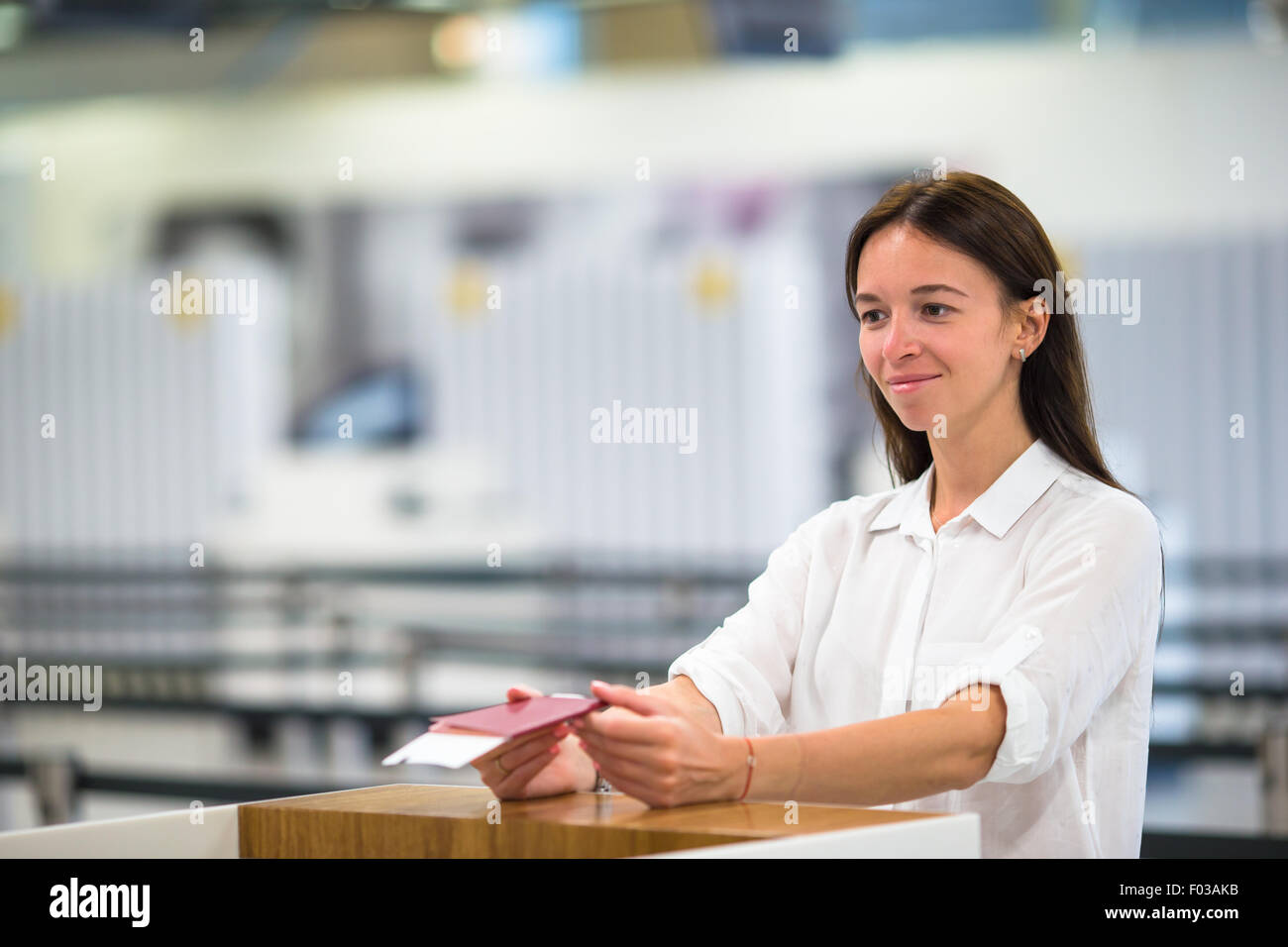 Beautiful woman with passports and boarding passes at the front desk at airport - Stock Image