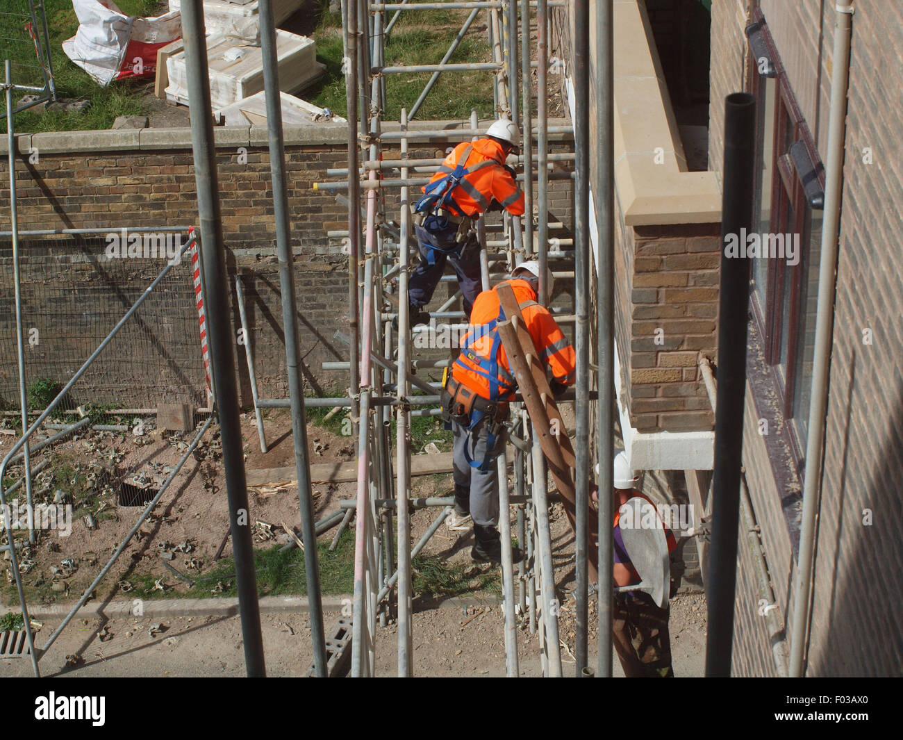 Scaffolders in the process of dismantling a spiders web of steel upon a listed building after renovation work has Stock Photo