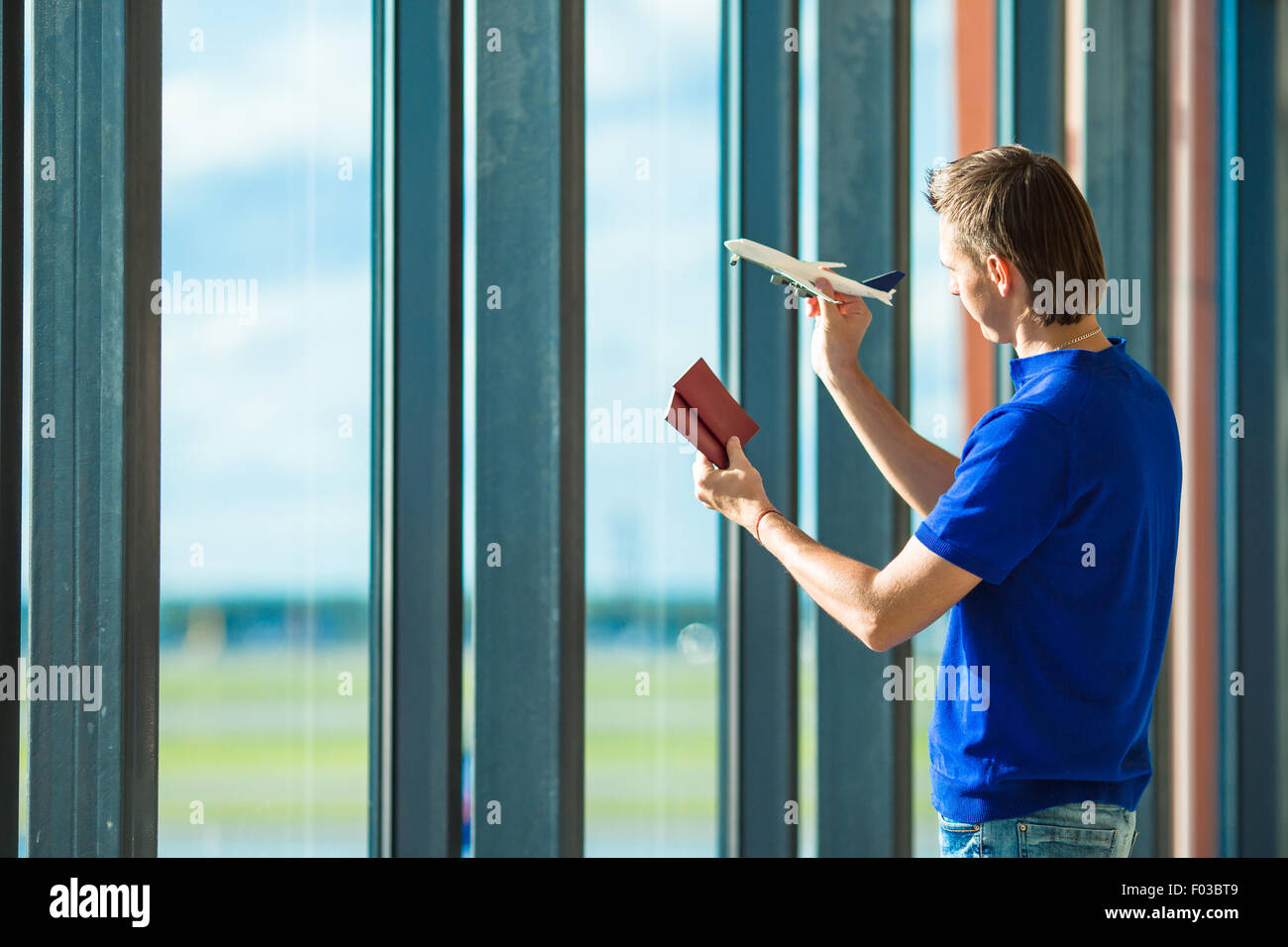 Young man with passports, boarding pass and aircraft toy model at airport - Stock Image