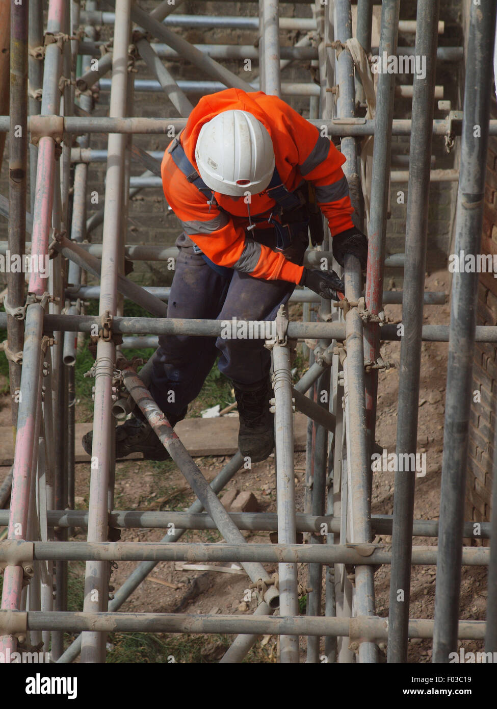 Scaffolders in the process of dismantling a spiders web of steel upon a listed building after renovation work has - Stock Image