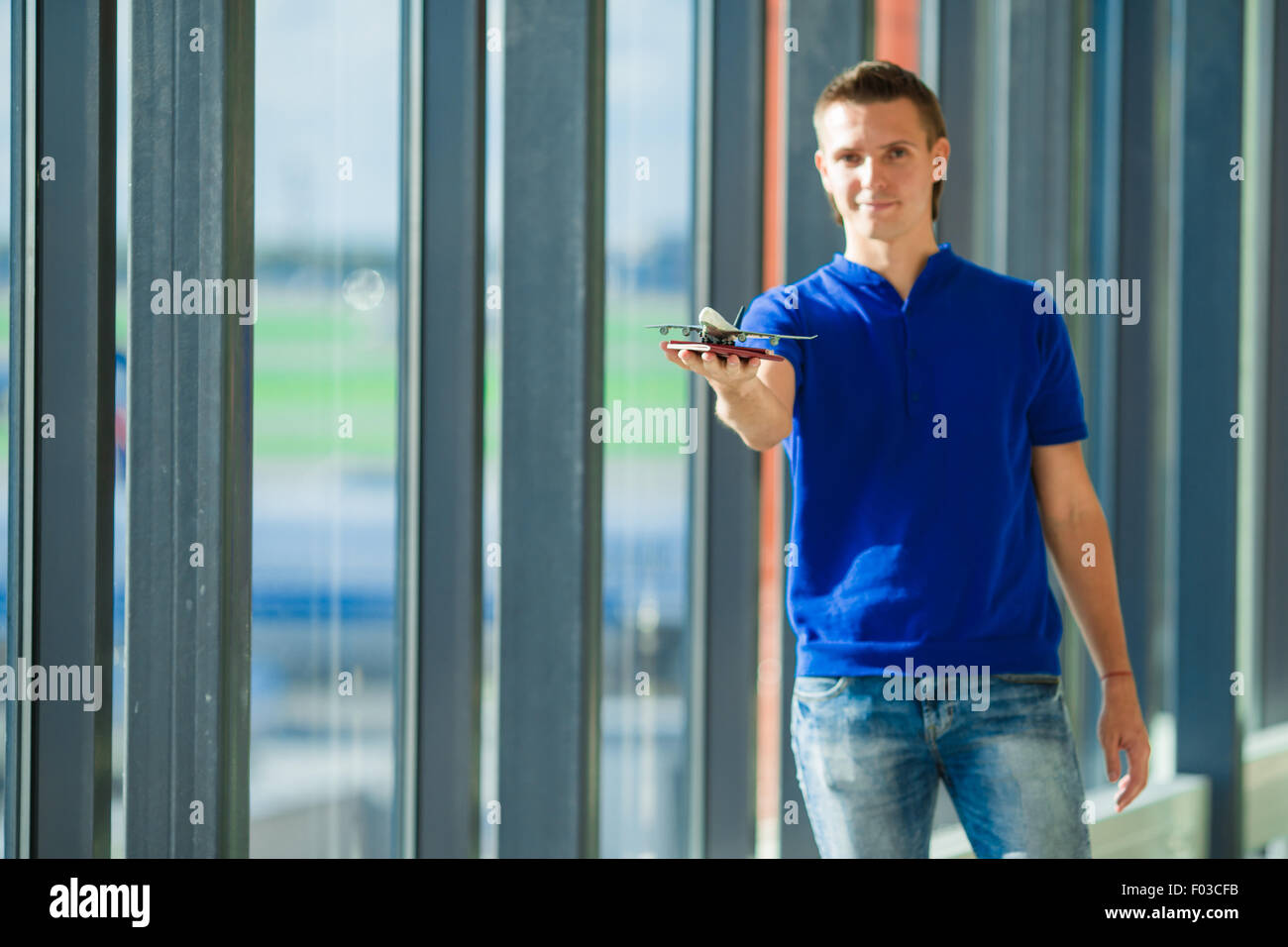 Young caucasian man holding passports and boarding pass at airport near window - Stock Image