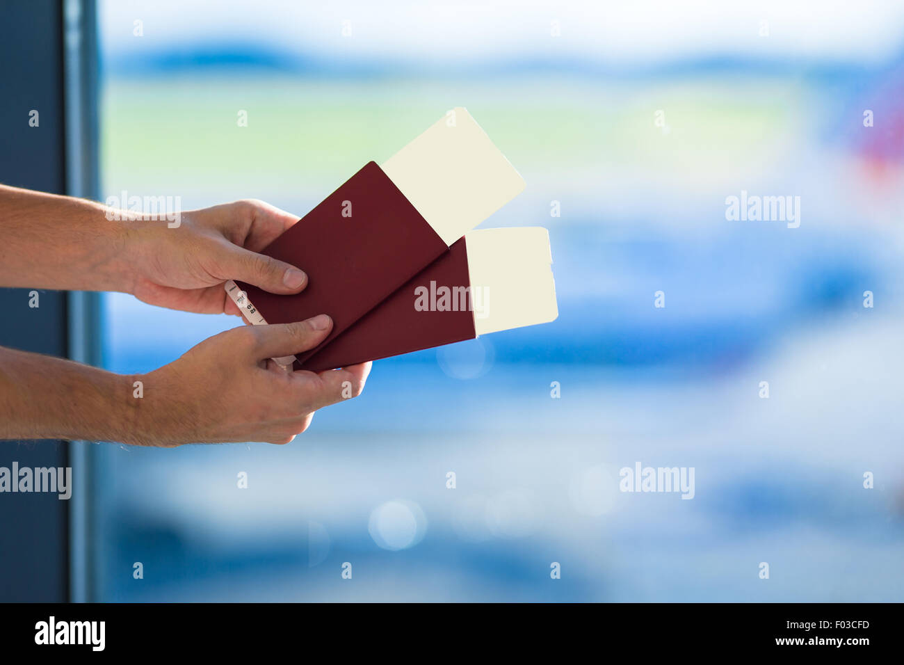 Closeup passports and boarding pass at airport indoor background airplane - Stock Image