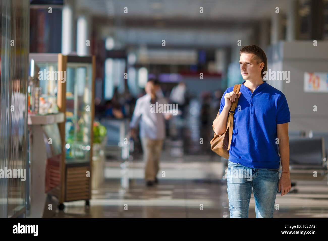 Young caucasian man at airport indoor waiting for boarding - Stock Image
