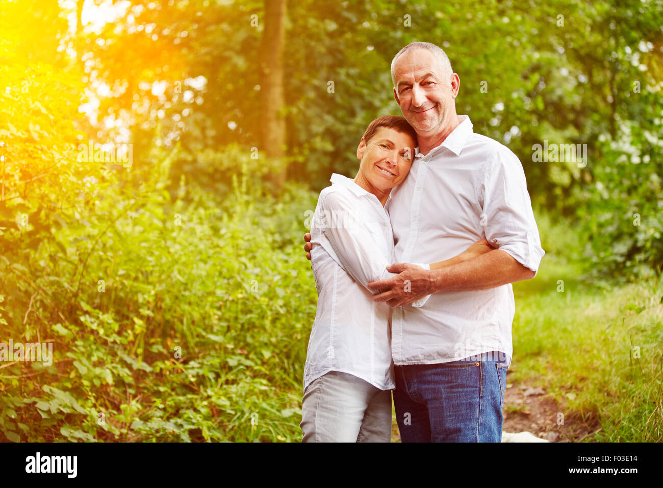 Happy smiling senior couple standing in a forest in summer - Stock Image