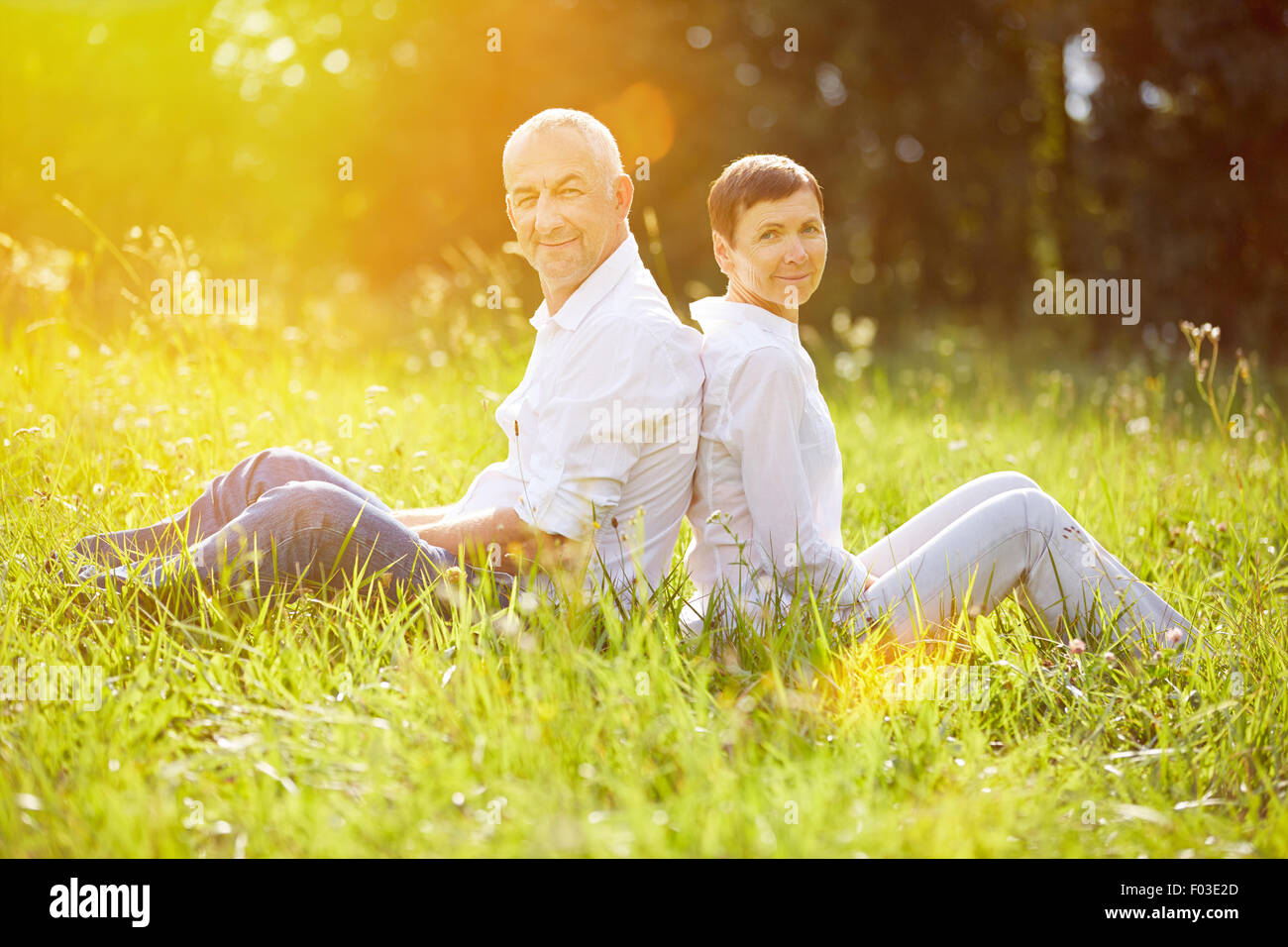 Happy senior couple relaxing on vacation in summer on a meadow - Stock Image