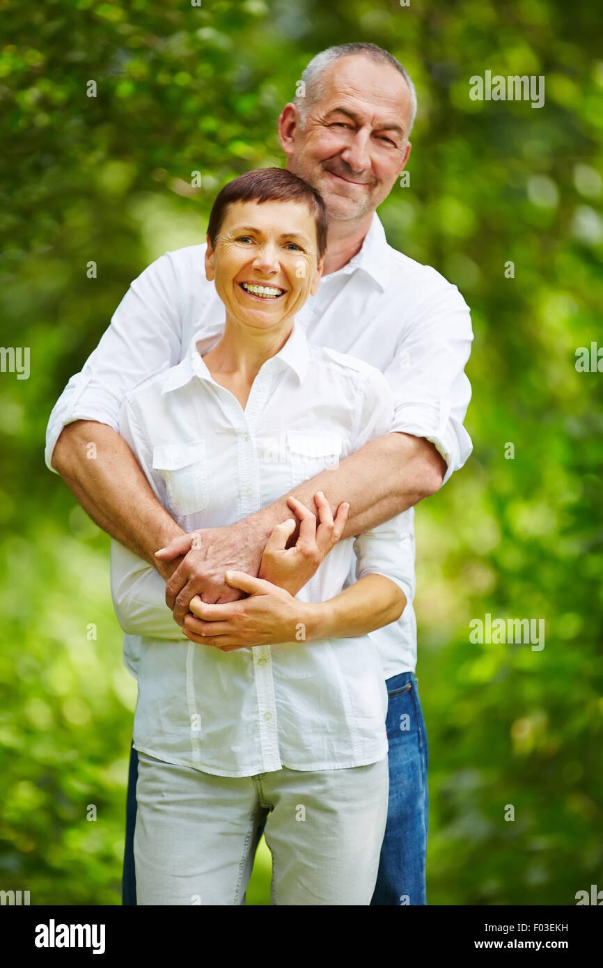 Happy senior couple standing together in nature - Stock Image