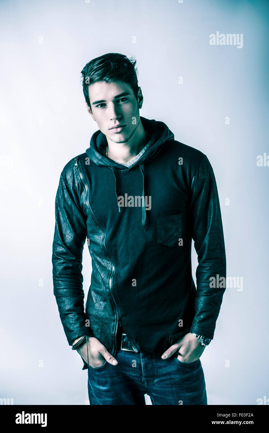 1722b6b8 Handsome young man in black hoodie sweater on light background, looking at  camera. Studio shot