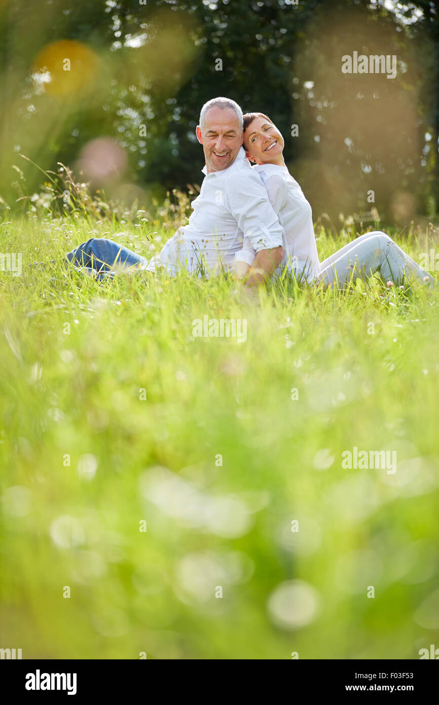 Happy senior couple sitting in grass in summer in nature - Stock Image