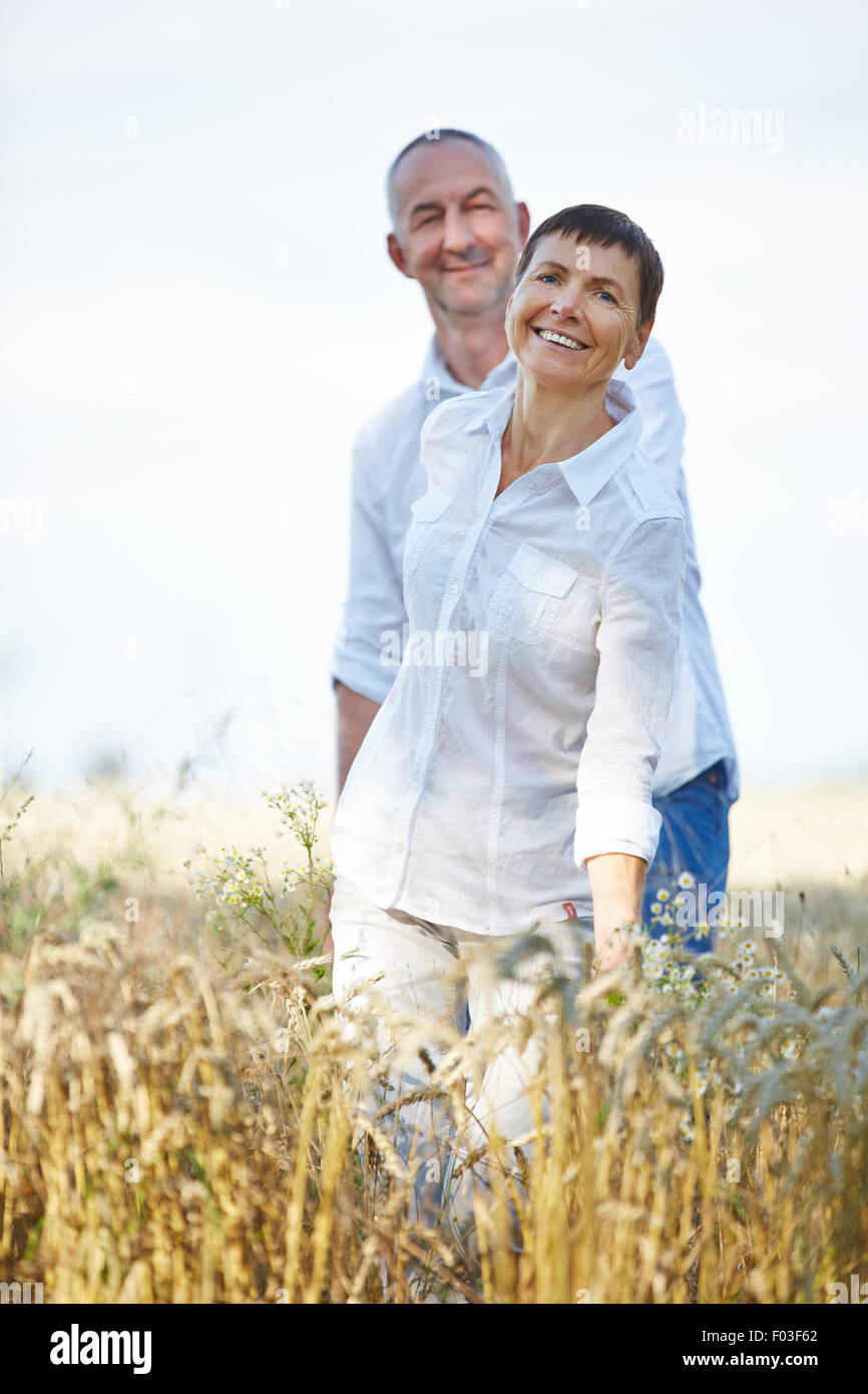 Happy senior couple on summer holiday walking through a wheat field - Stock Image