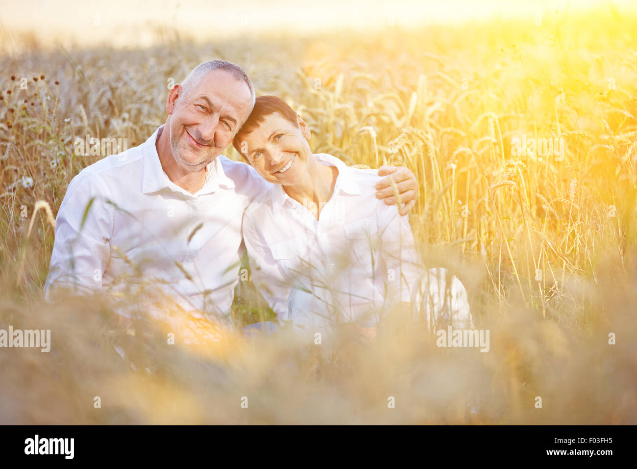 Happy senior couple on summer vacation sitting in a wheat field - Stock Image