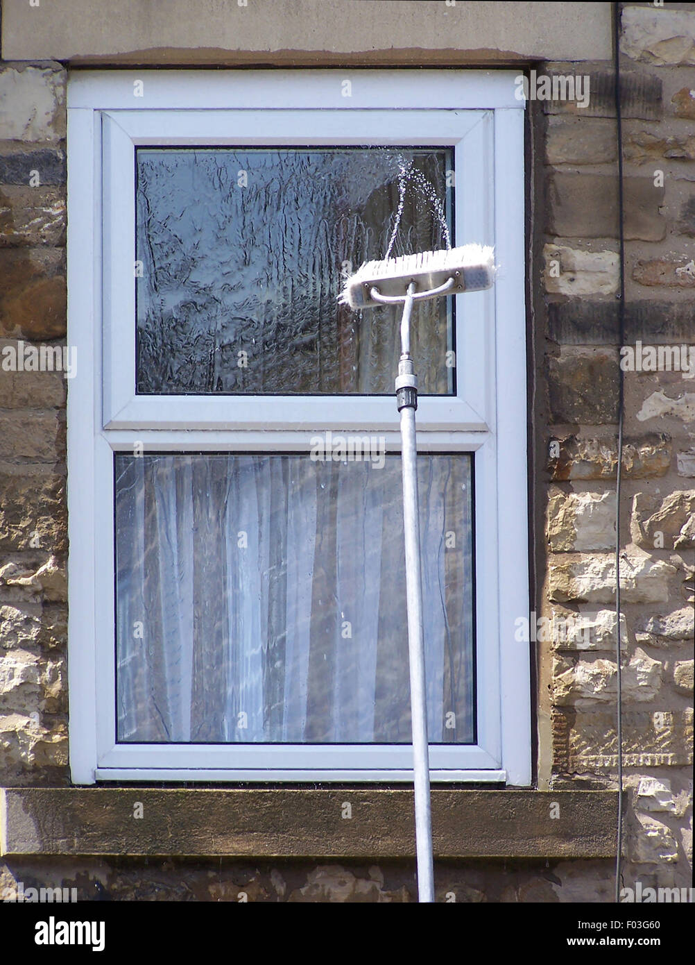 Window cleaning brush squirts water onto window - Stock Image