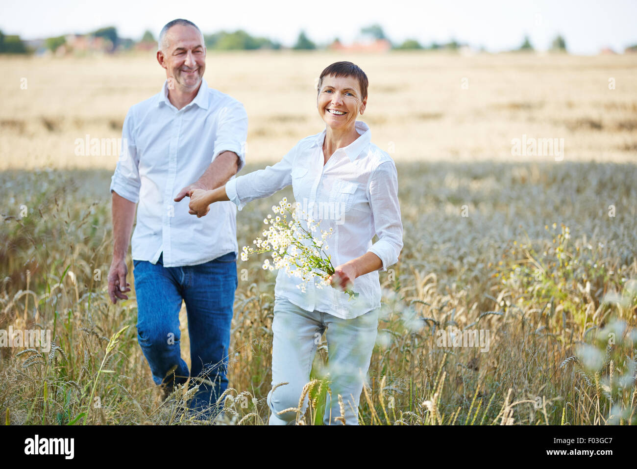 Senior couple with flowers walking in nature in summer - Stock Image