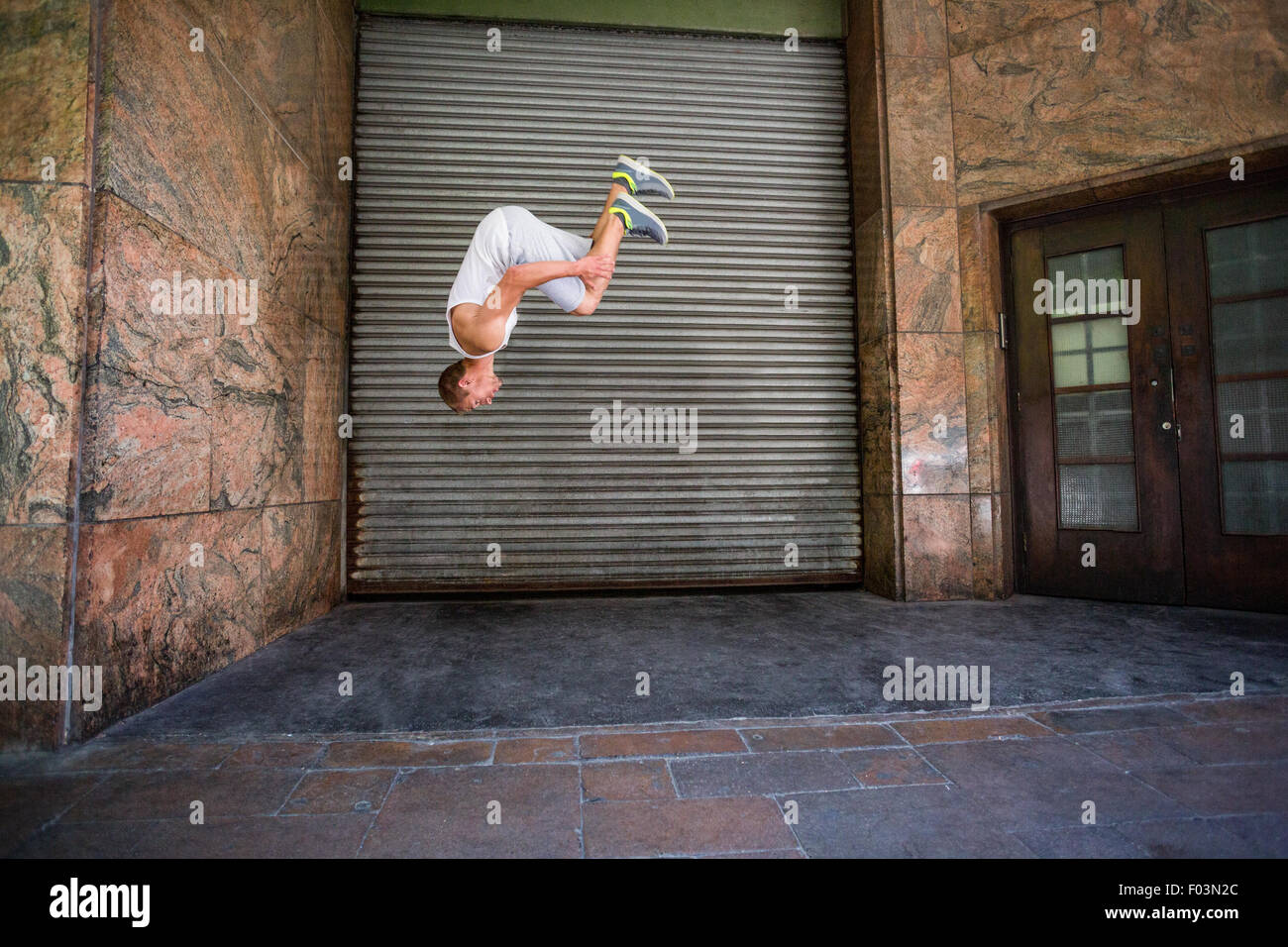 Extreme athlete doing a front flip in front of a building - Stock Image