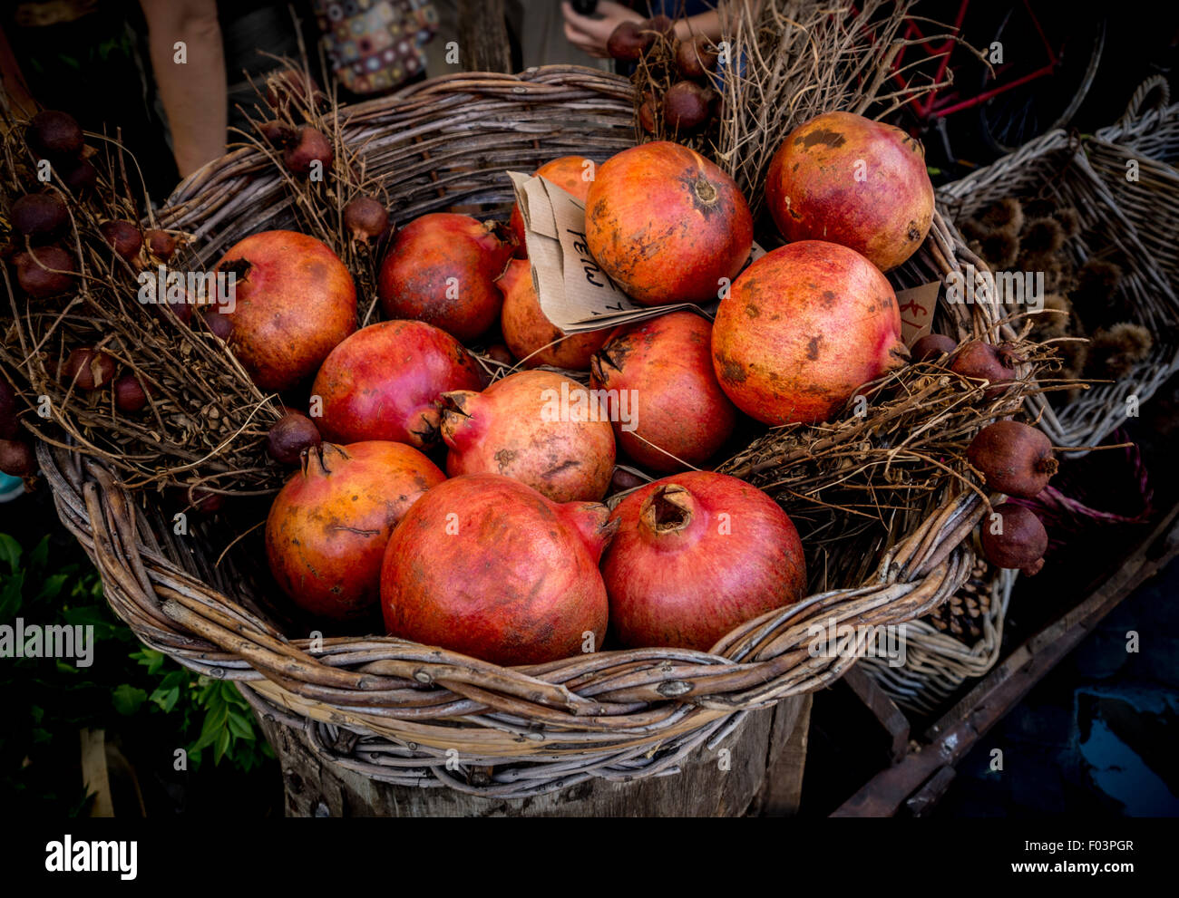 Basket of fresh pomegranates at Campo de' Fiori outdoor food market in Rome., Italy. - Stock Image