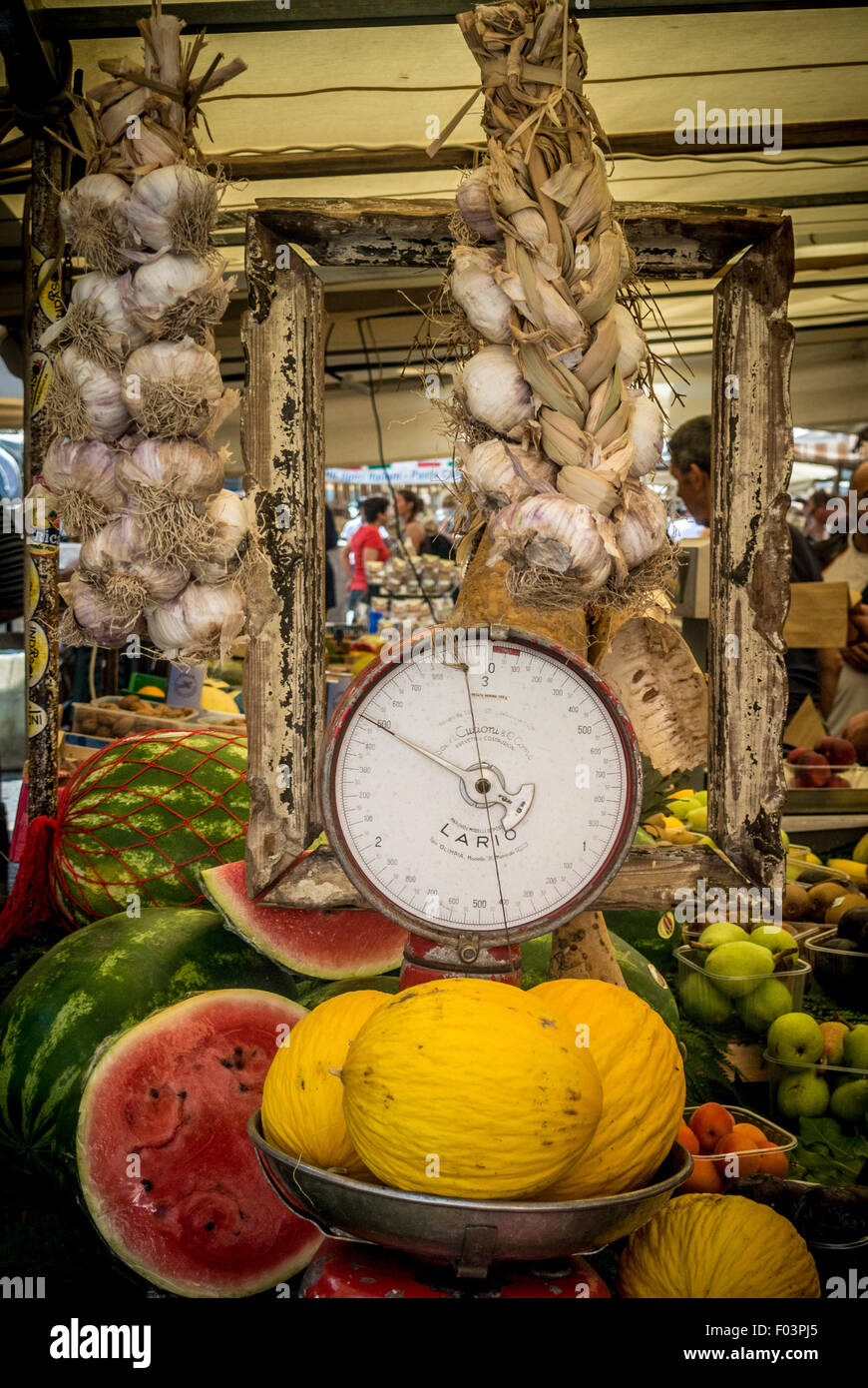 Honeydew melons displayed on old fashioned weighing scales at Campo de' Fiori outdoor food market in Rome., - Stock Image