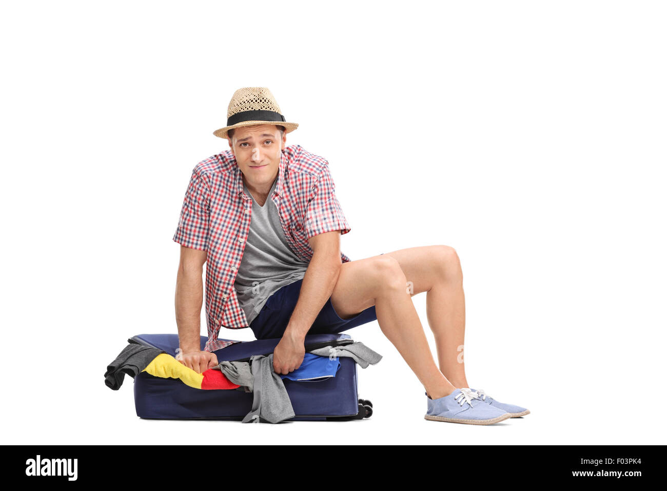 Sad young male tourist sitting on top of a packed suitcase and trying to close it isolated on white background - Stock Image