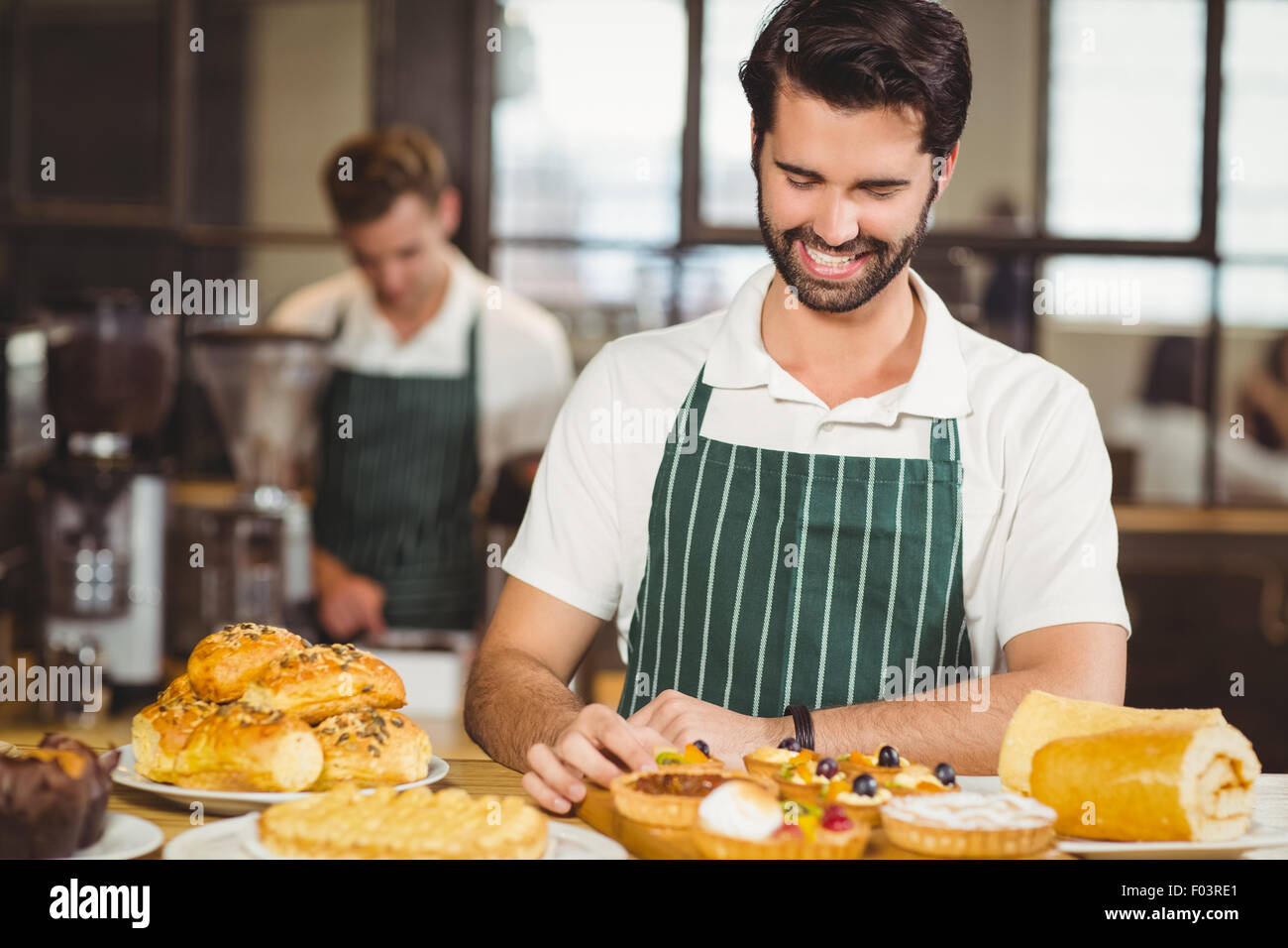 Smiling waiter tidying up the pastries - Stock Image