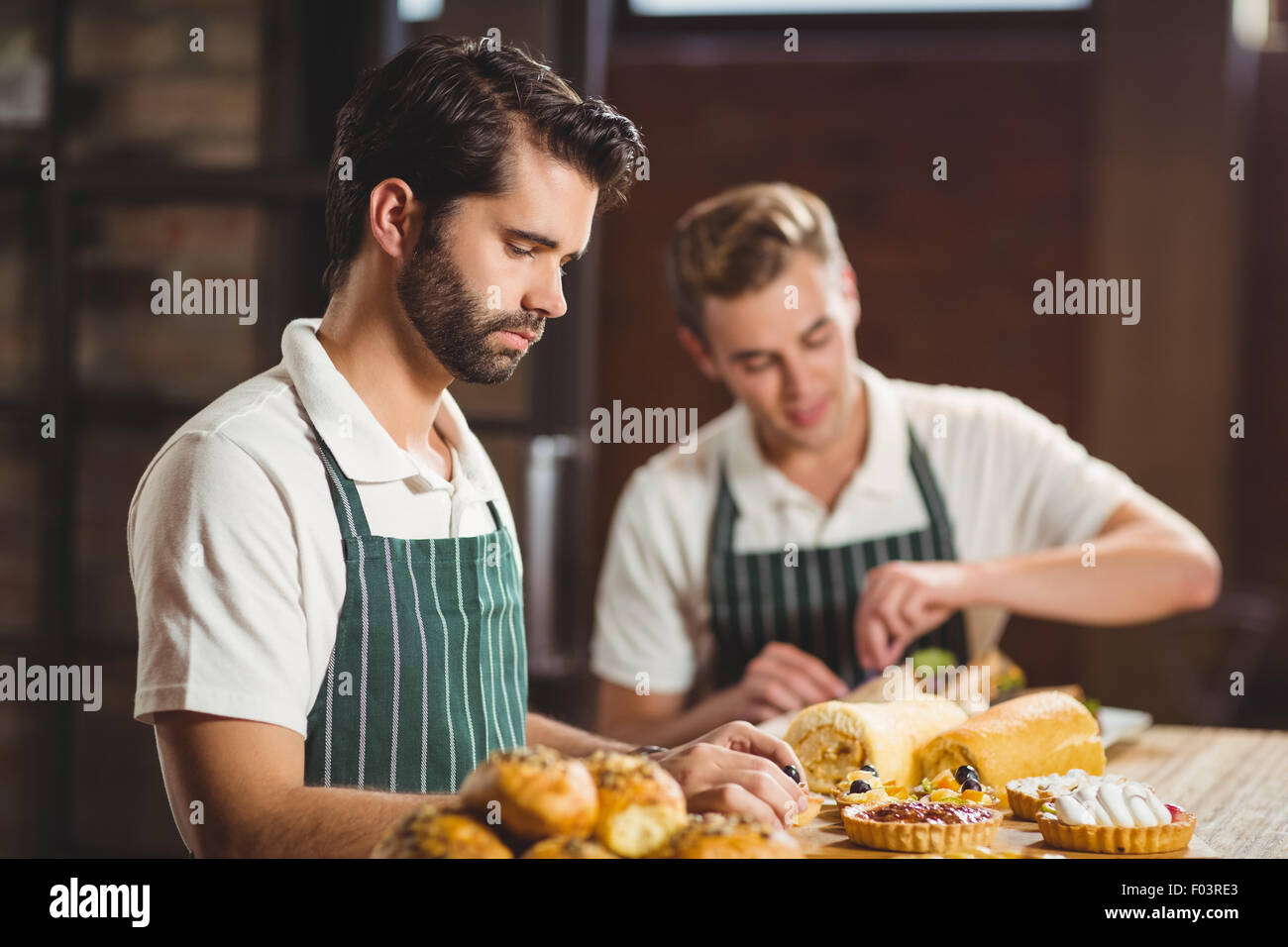 Concentrated waiters tidying up the pastries - Stock Image