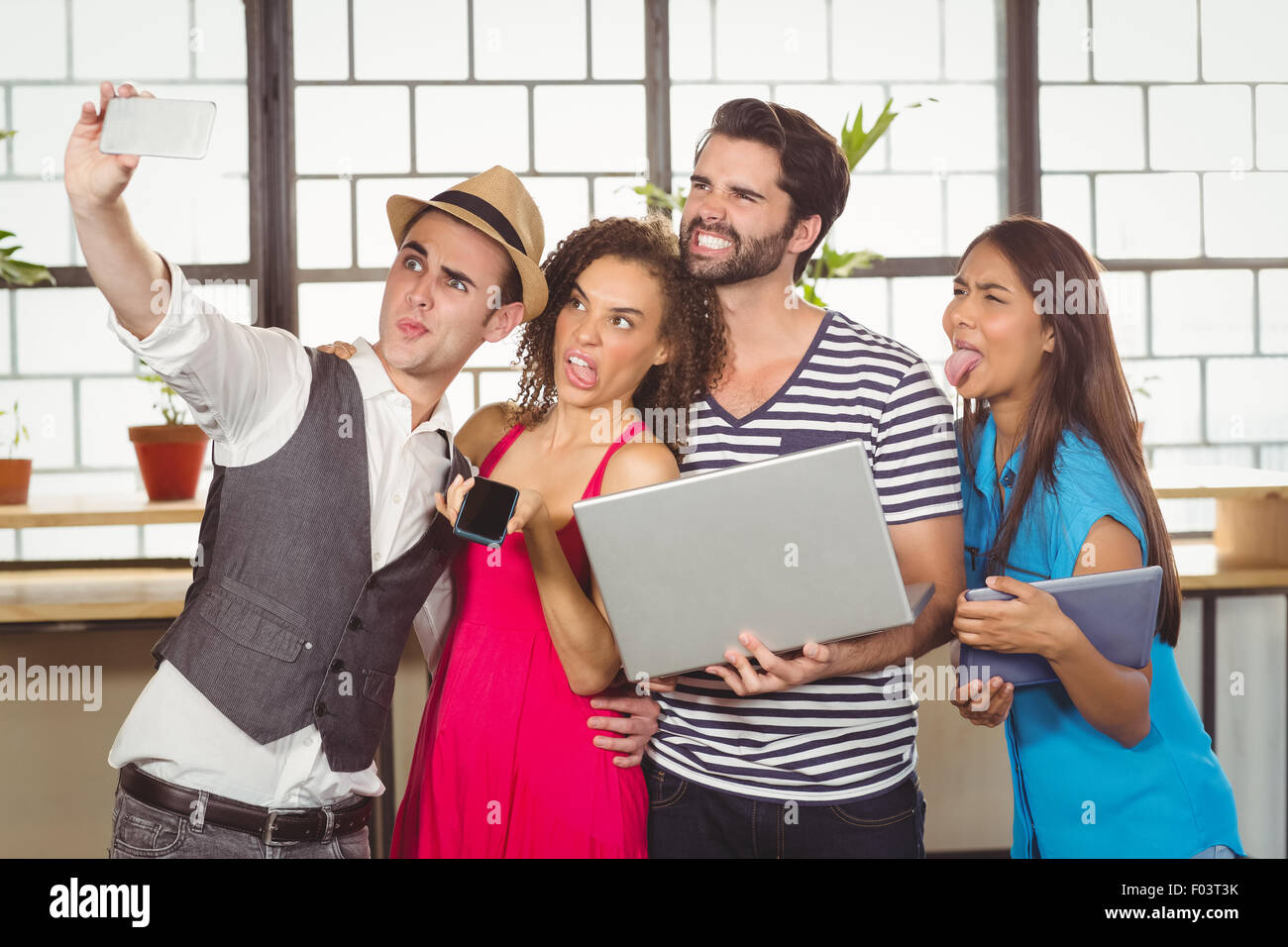 Grimacing friends taking selfies - Stock Image