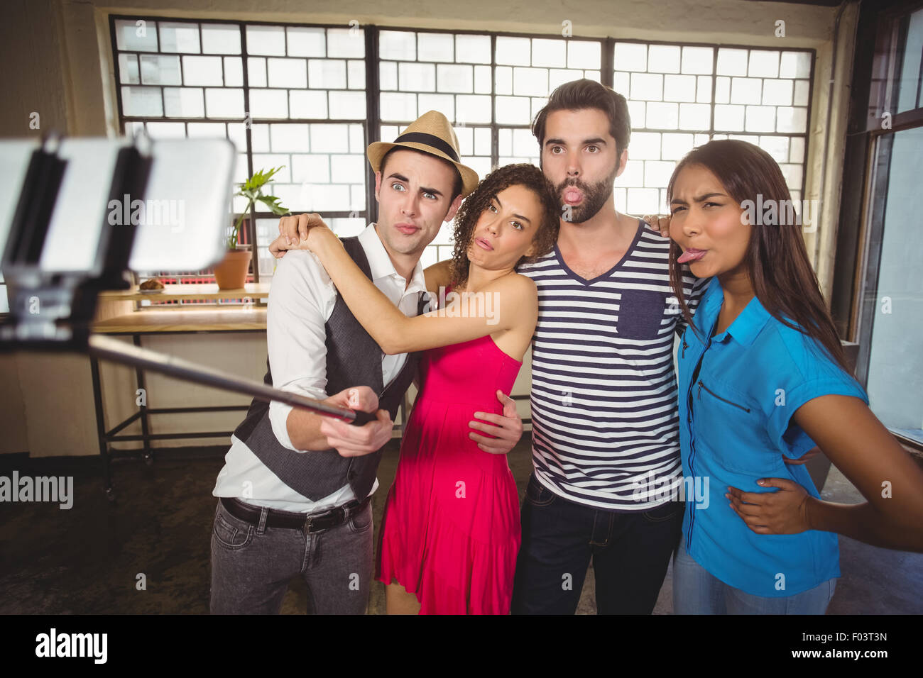 Grimacing friends taking selfies with selfiestick - Stock Image