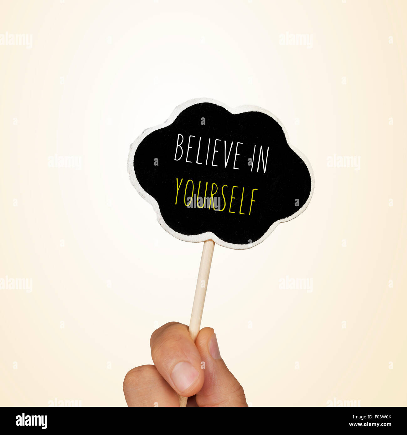 closeup of the hand of a young woman holding a chalkboard in the shape of a thought bubble with the text believe - Stock Image