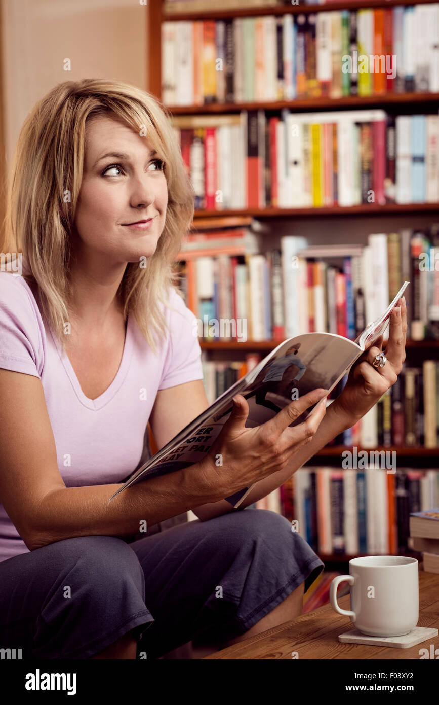 Woman reading at home - Stock Image
