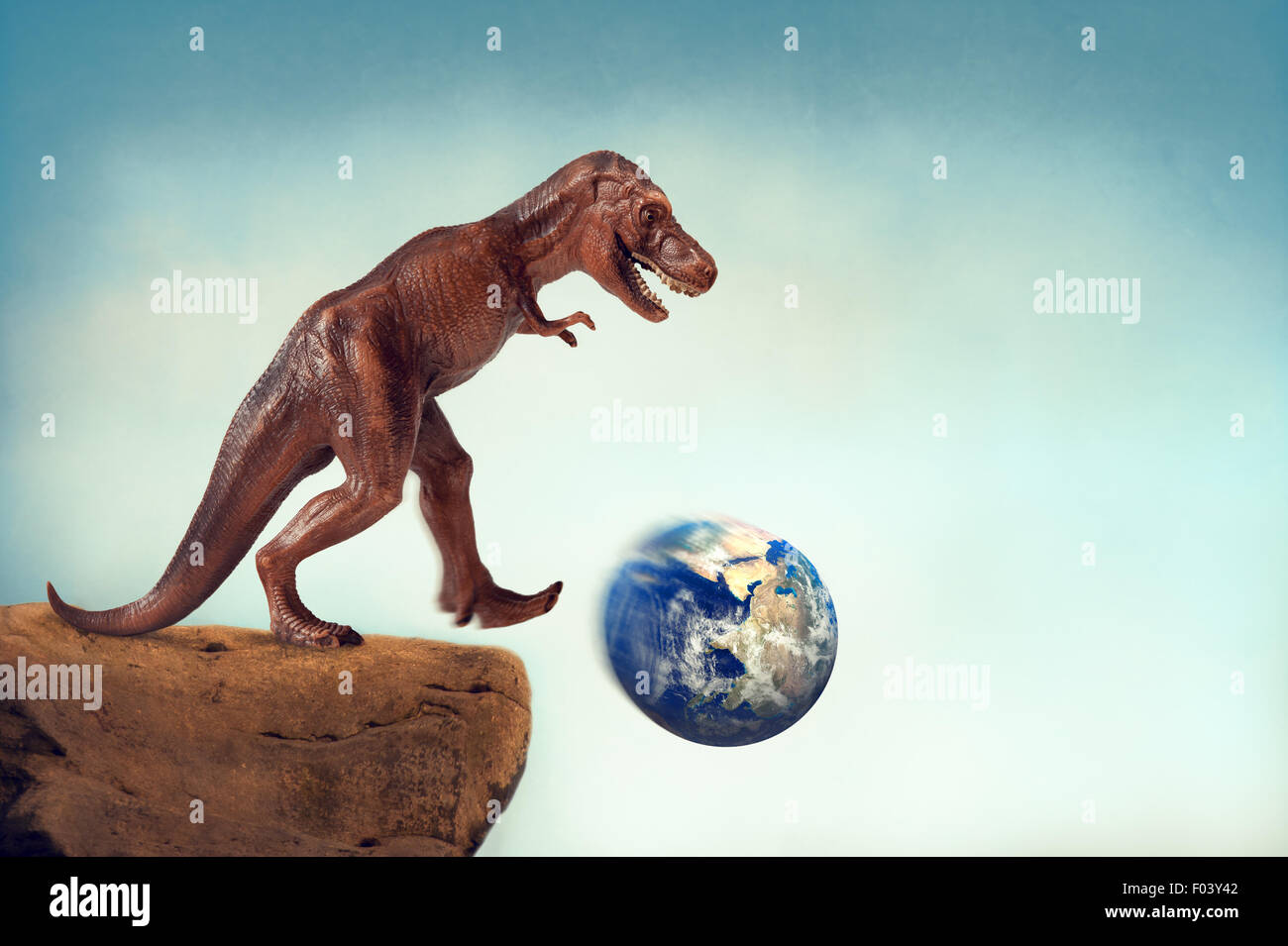 extinction or sustainability concept dinosaur kicking the planet earth off a precipice - Stock Image