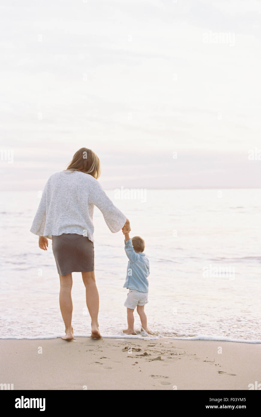 Woman standing on a sandy beach by the ocean, holding her young son's hand. - Stock Image