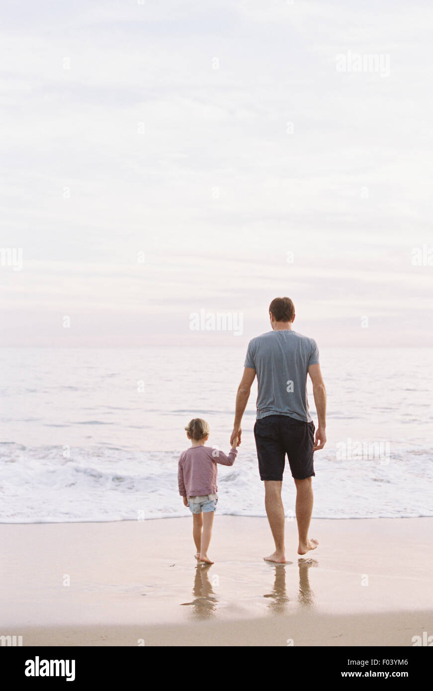 Man standing on a sandy beach by the ocean, holding his young daughter's hand. - Stock Image