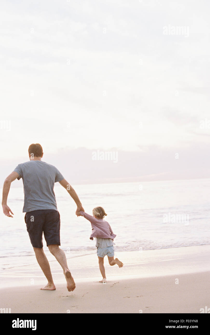 Man playing on a sandy beach by the ocean, holding his young daughter's hand. - Stock Image
