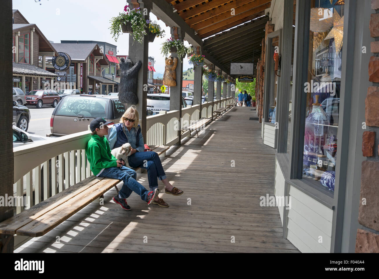 A woman and her son sitting on the bench with small white dog,  Jackson, Wyoming,  USA - Stock Image
