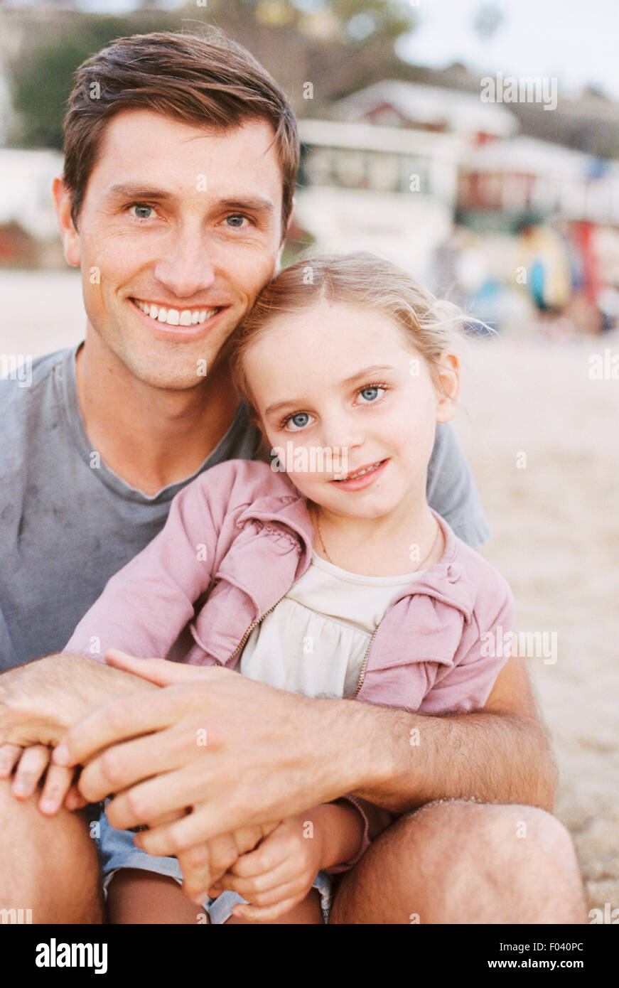 Young girl sitting on her father's lap, looking at camera, smiling. - Stock Image