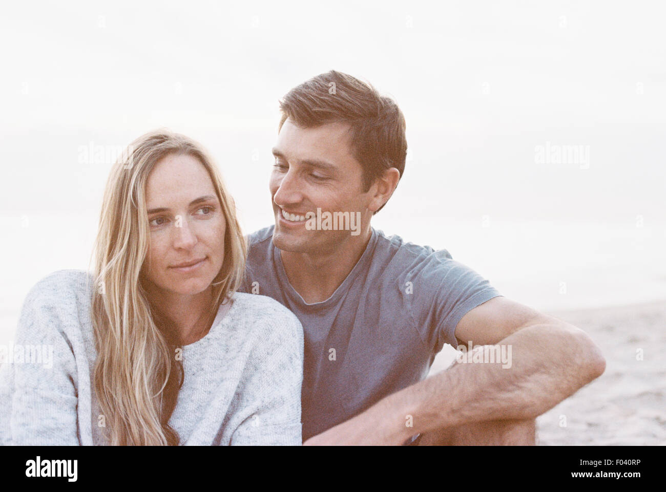 A couple sitting close on a beach, a man and woman with their arms around each other and heads together. - Stock Image