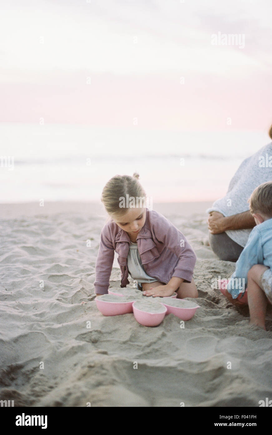 Young boy and girl playing in the sand on a beach beside an adult couple. - Stock Image