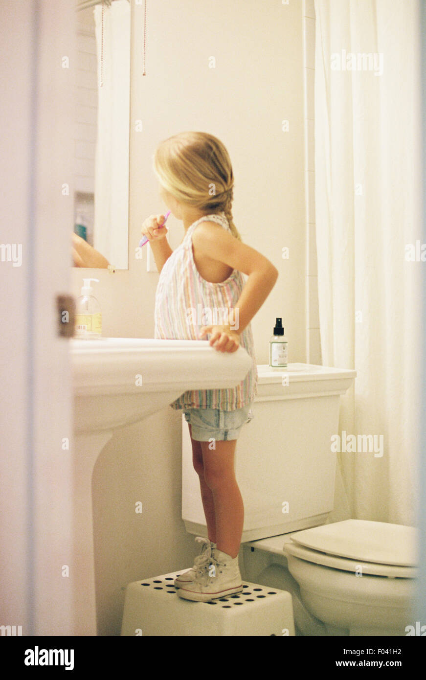 Young girl standing on a stool in a bathroom, brushing her teeth. - Stock Image