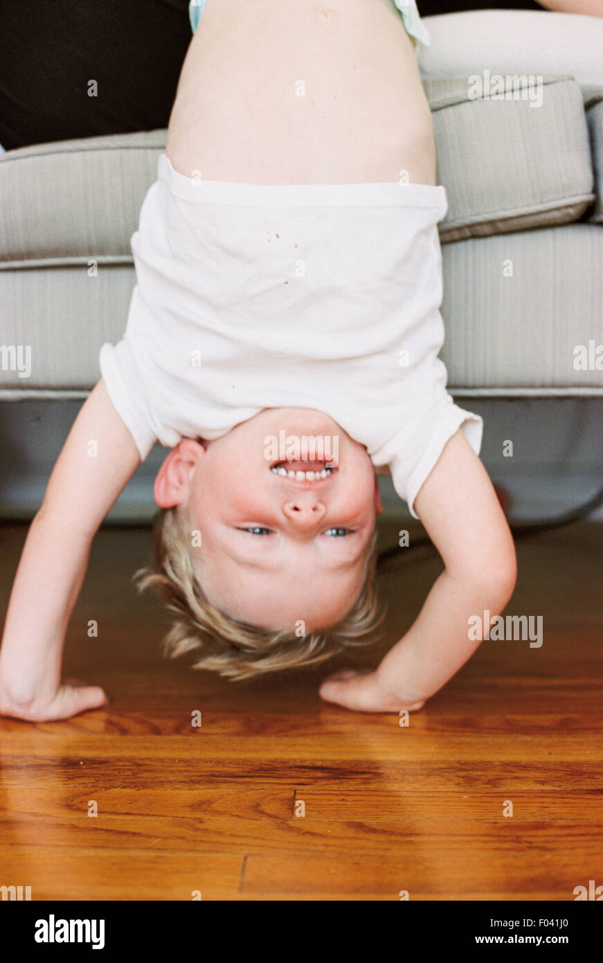 Young boy doing a handstand in front of a sofa. - Stock Image
