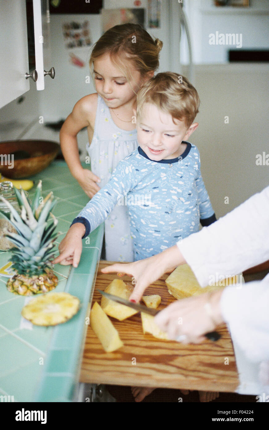 Woman cutting a fresh pineapple for her children. - Stock Image
