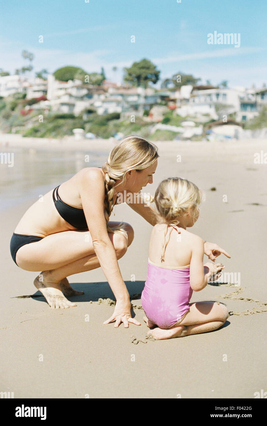 Woman in a bikini playing with her daughter on a sandy beach. - Stock Image