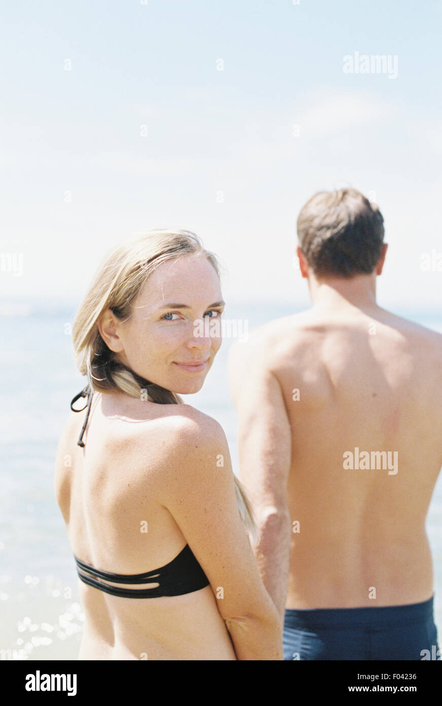Couple in swimwear by the ocean, woman smiling at camera. - Stock Image