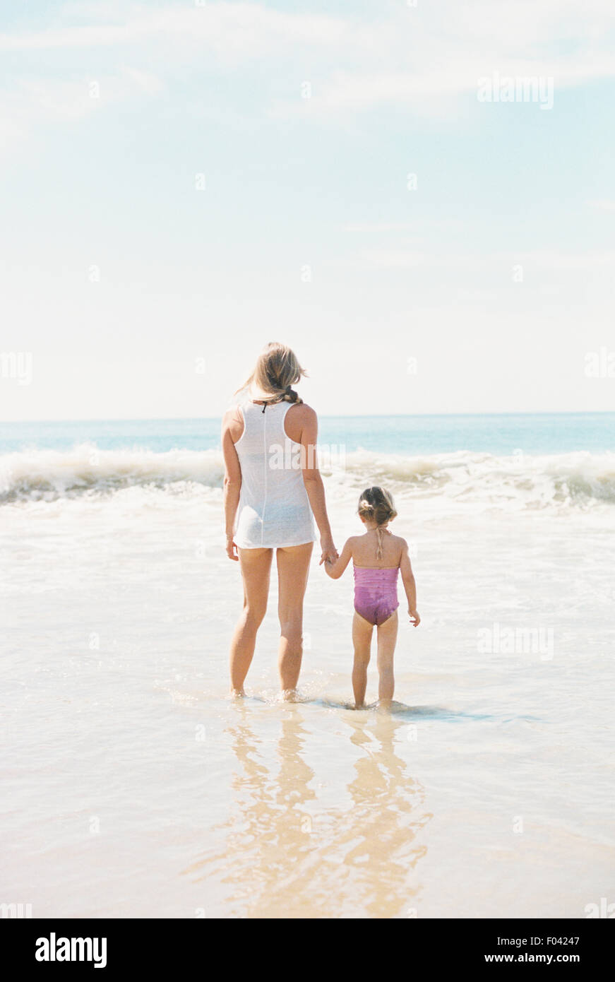 Woman standing hand in hand with her daughter on a sandy beach. - Stock Image