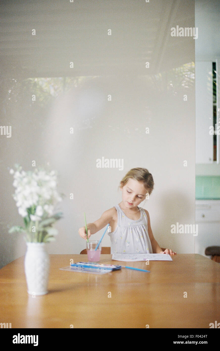 Young girl sitting at  a table, painting, a vase with white flowers. - Stock Image