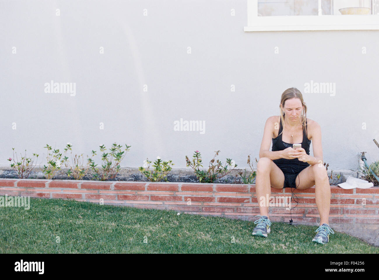 Blond woman in sportswear sitting on a garden wall, resting after a jog. - Stock Image