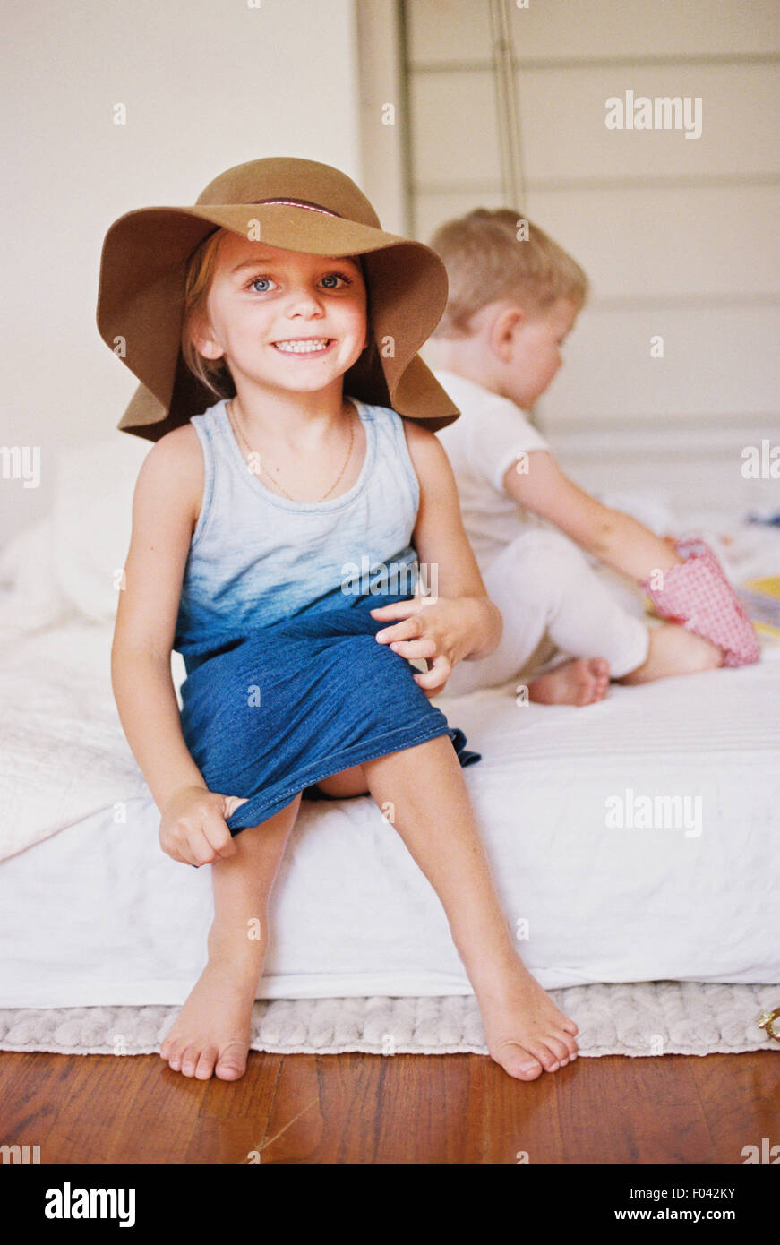 Young girl wearing a dress and large floppy hat on a bed with her younger brother. - Stock Image