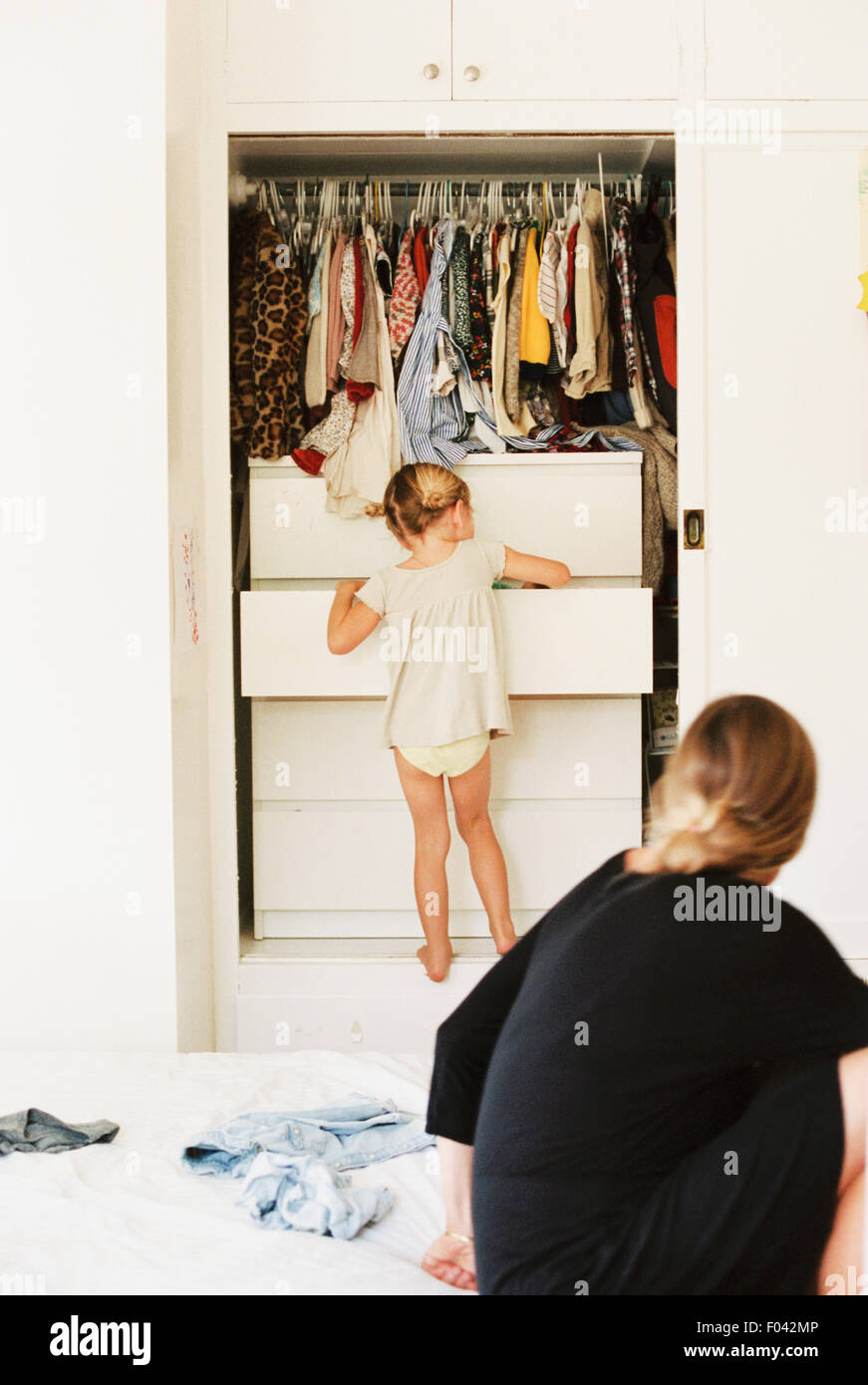 Young girl looking for clothes in a chest of drawers, her mother sitting on a bed, watching. - Stock Image